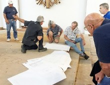 Architect David Huboi meets with contractors over plans for church altar.